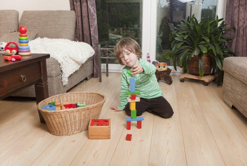 Menino que joga com blocos de apartamentos fotografia de stock royalty free