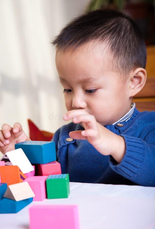 menino que joga com blocos de madeira fotografia de stock