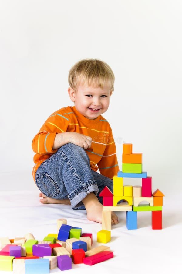 Menino que joga com blocos de madeira foto de stock