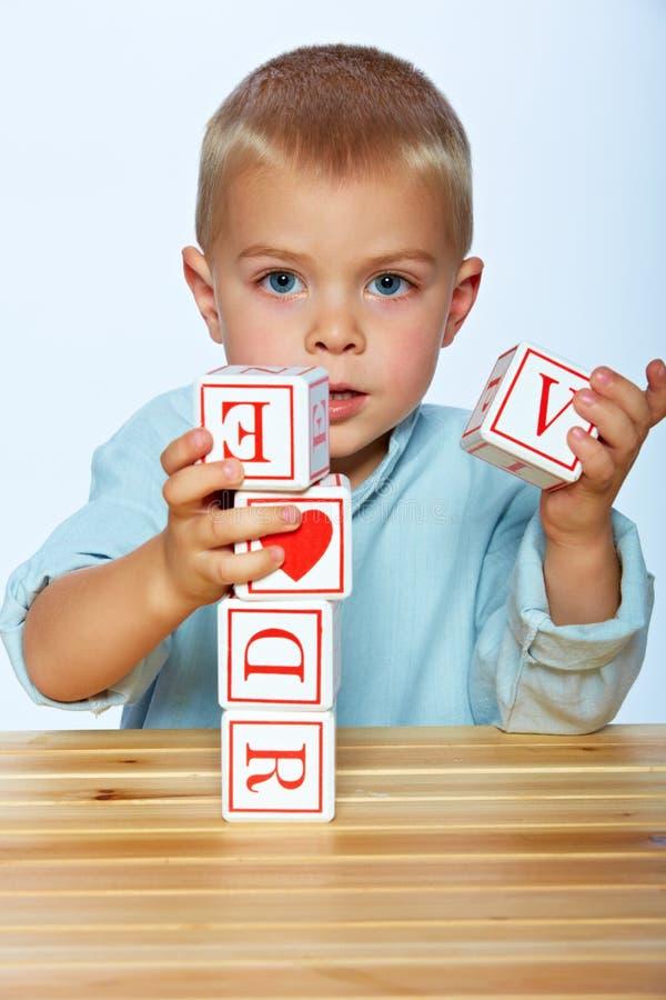 Menino que joga com blocos do alfabeto fotos de stock royalty free