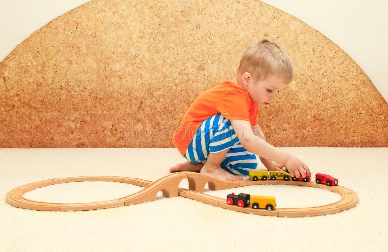 Menino que joga com brinquedo da estrada de ferro fotografia de stock