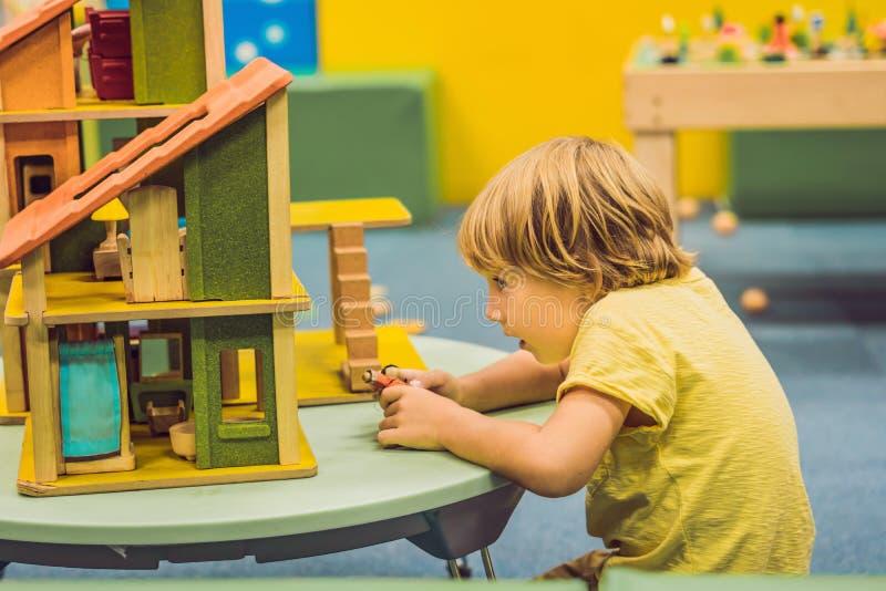 Menino que joga com a casa de madeira no jardim de infância fotografia de stock royalty free