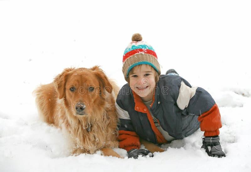 Menino que joga com o cão na neve fotos de stock royalty free