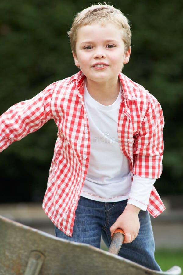 Menino que joga com o carrinho de mão no jardim foto de stock