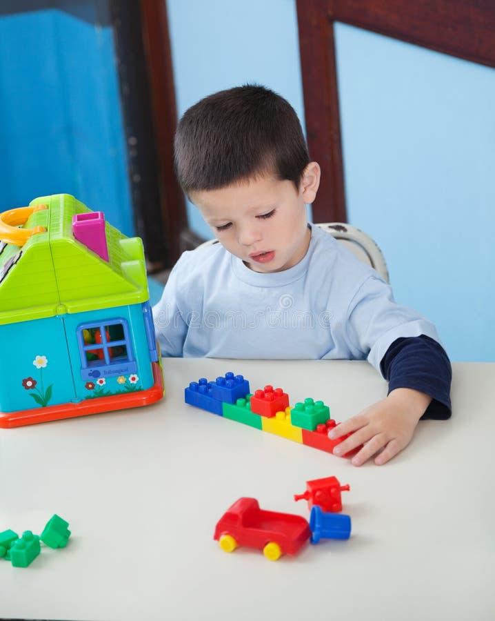 Menino que joga com os brinquedos na mesa no pré-escolar imagem de stock royalty free