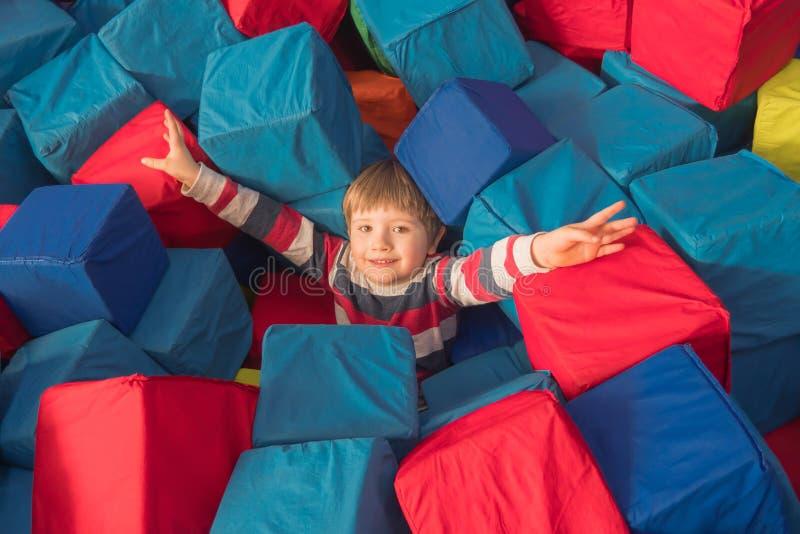 Menino que joga com os cubos macios na associação seca da sala de crianças do jogo para o aniversário centro de entretenimento in fotos de stock royalty free