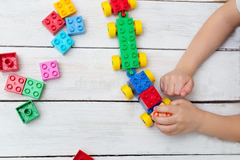 Menino que joga com os tijolos plásticos coloridos na tabela Configuração lisa imagens de stock royalty free