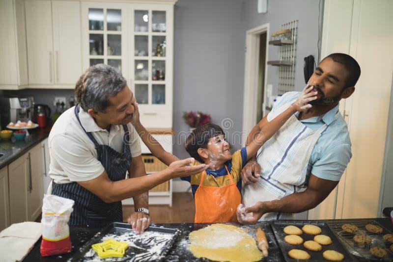 Menino que joga com pai e avô ao preparar o alimento na cozinha fotografia de stock royalty free