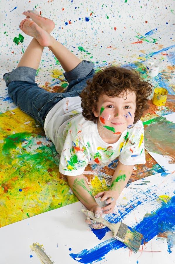 Menino que joga com pintura fotos de stock