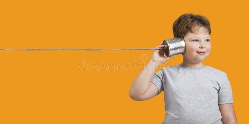 Menino que joga com Tin Can Phone Isolado no fundo alaranjado imagem de stock royalty free