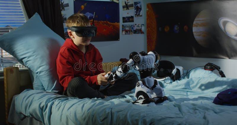 Menino que joga com um robô do brinquedo imagem de stock royalty free