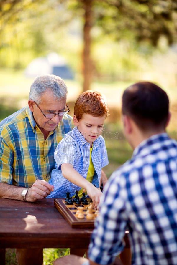 Menino que joga a estratégia da xadrez imagem de stock