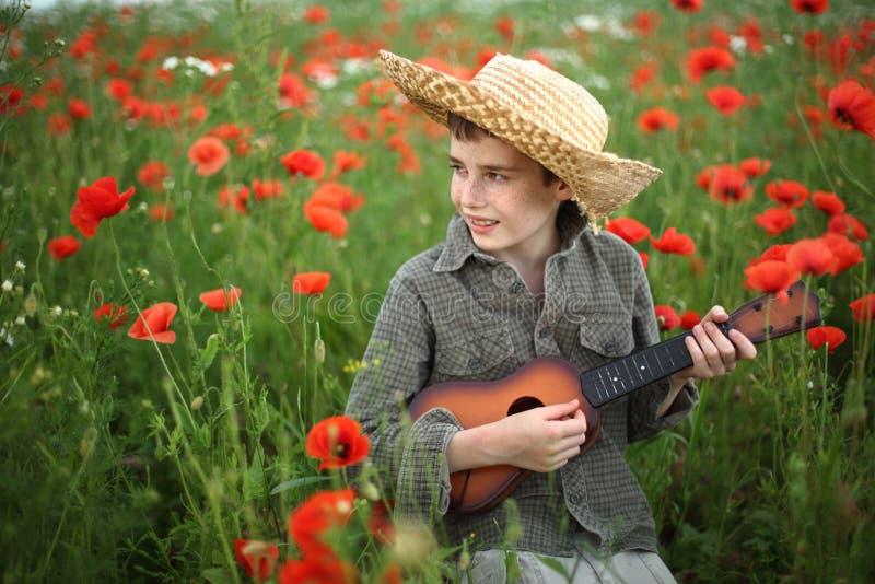 Menino que joga a guitarra fotografia de stock