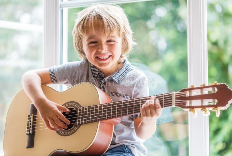 Menino que joga a guitarra acústica foto de stock royalty free