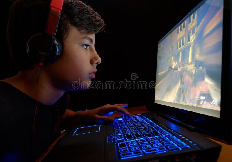 Menino que joga jogos em seu portátil fotos de stock royalty free