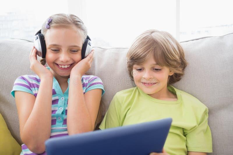 Menino que joga a música no portátil para a irmã em casa foto de stock royalty free