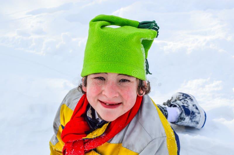 Menino que joga na neve com chapéu verde fotografia de stock