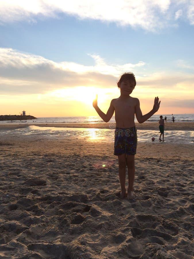 Menino que joga na praia no por do sol fotografia de stock