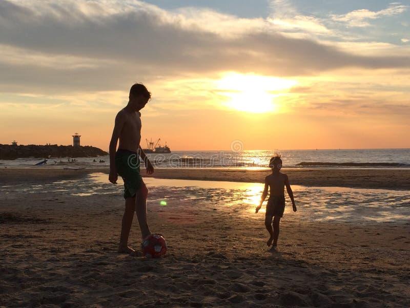 Menino que joga na praia no por do sol imagens de stock