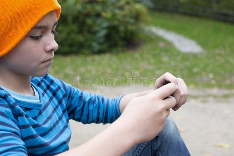Menino que joga no telefone fotos de stock