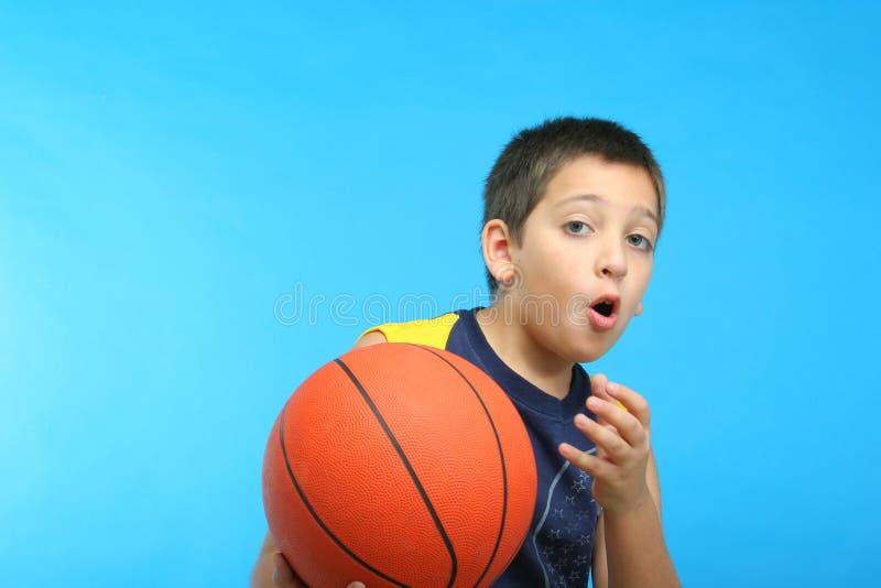 Menino que joga o basquetebol. Fundo azul foto de stock royalty free