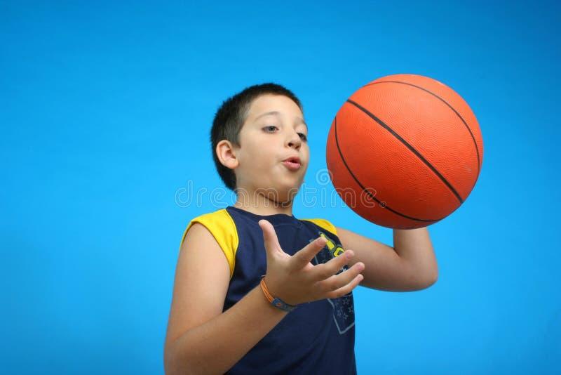 Menino que joga o basquetebol. fundo azul imagem de stock royalty free