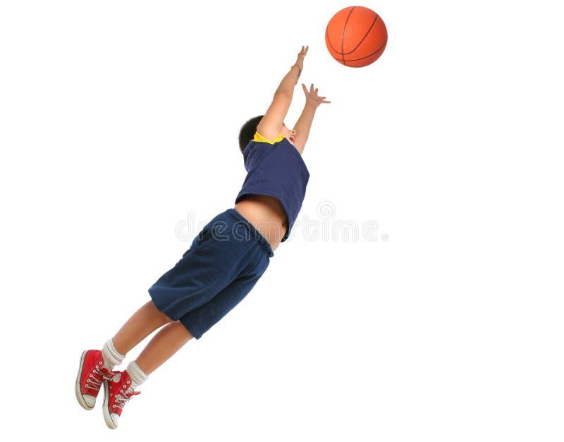 Menino que joga o basquetebol isolado. Voo e salto imagem de stock