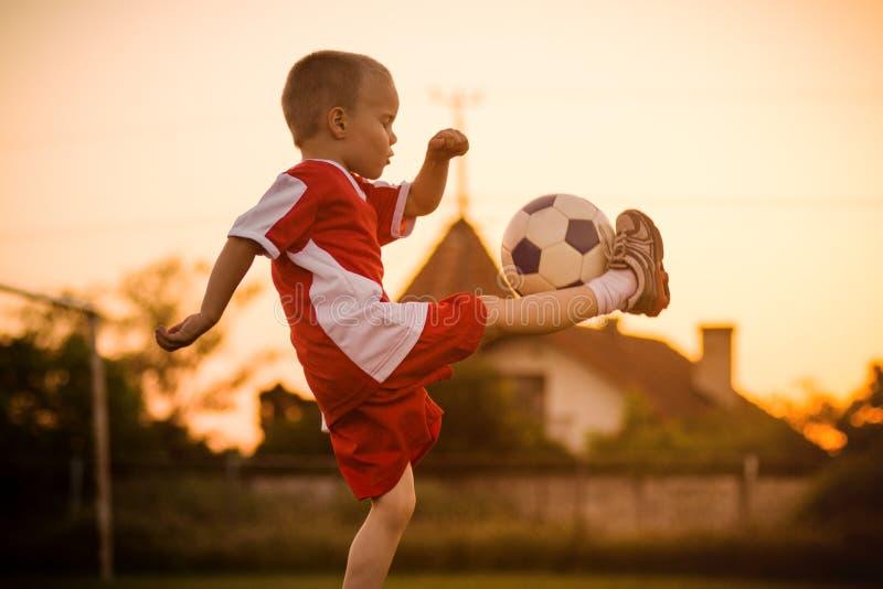 Menino que joga o futebol fotografia de stock
