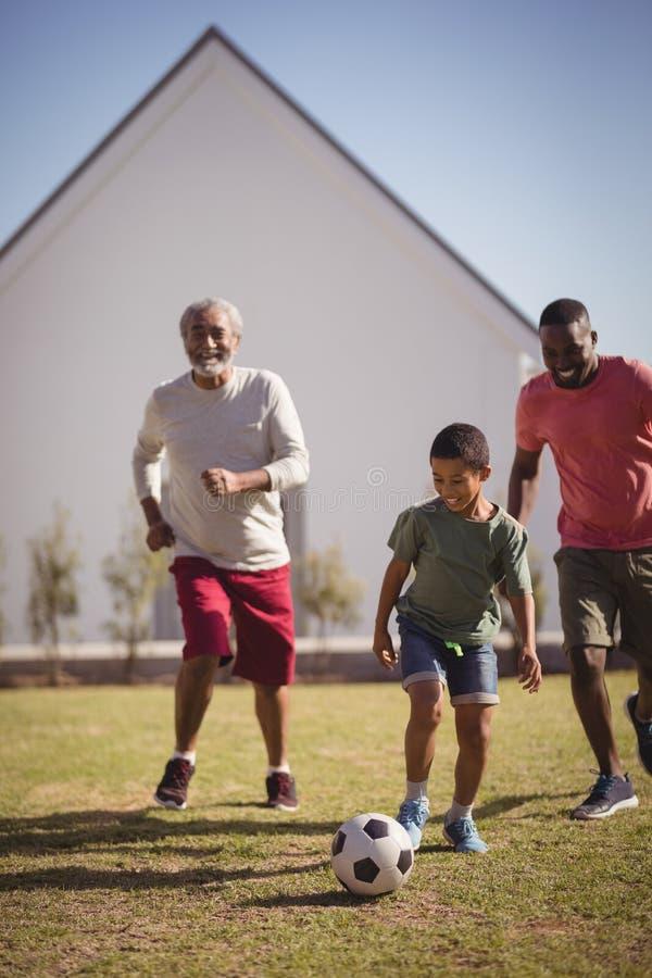 Menino que joga o futebol com seus pai e neto imagem de stock