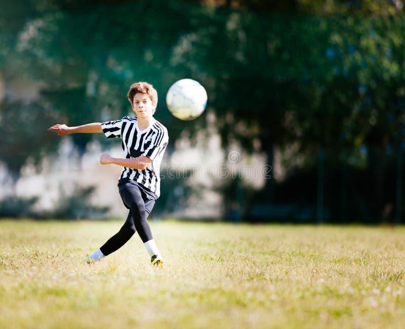 Menino que joga o futebol em um campo de futebol foto de stock royalty free