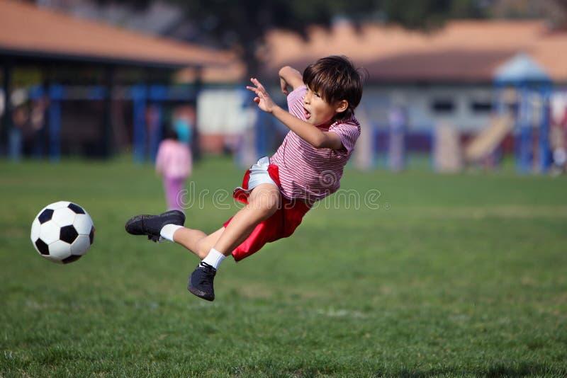 Menino que joga o futebol no parque imagem de stock royalty free
