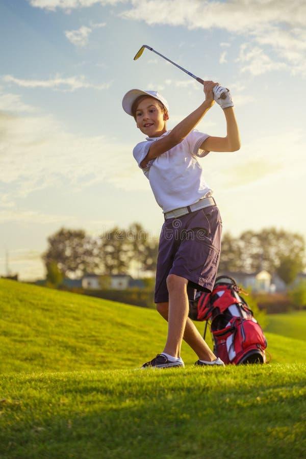 Menino que joga o golfe fotos de stock royalty free
