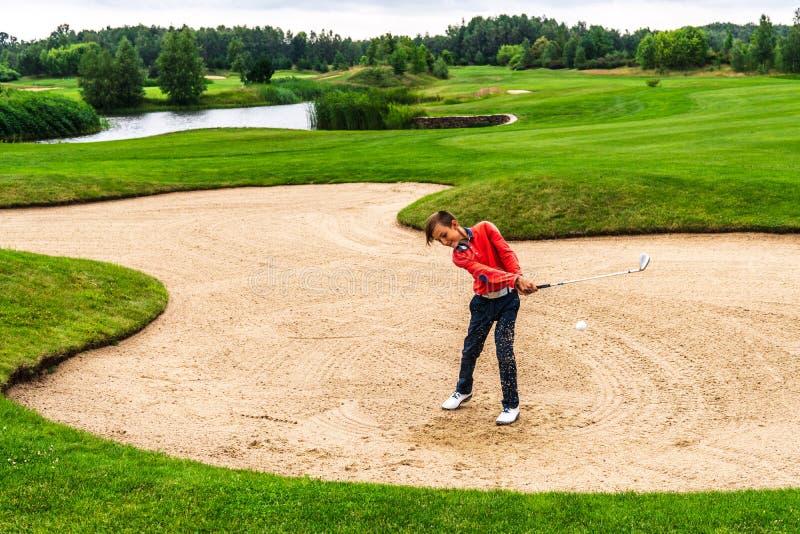 Menino que joga o golfe fotografia de stock royalty free