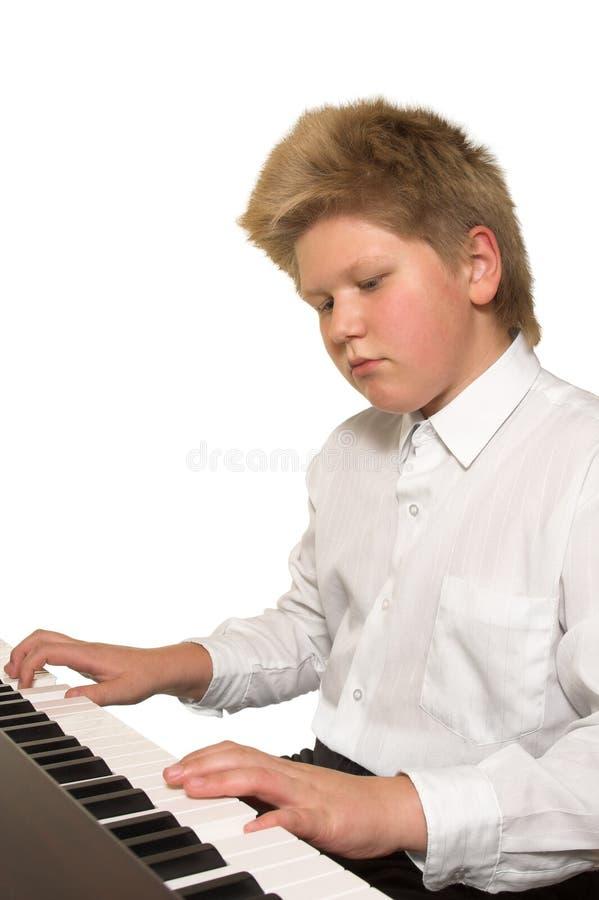Menino que joga o piano imagens de stock