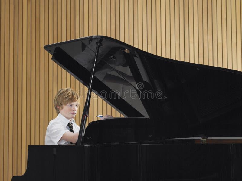 Menino que joga o piano na classe de música foto de stock royalty free