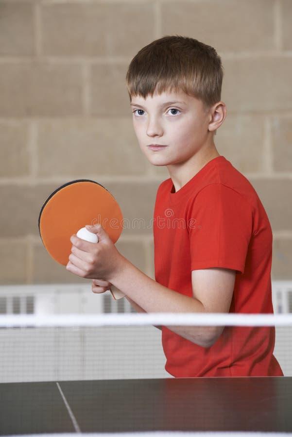 Menino que joga o tênis de mesa no Gym da escola foto de stock royalty free
