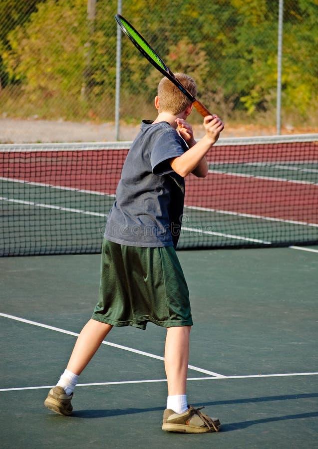 Menino que joga o tênis - golpe fotografia de stock