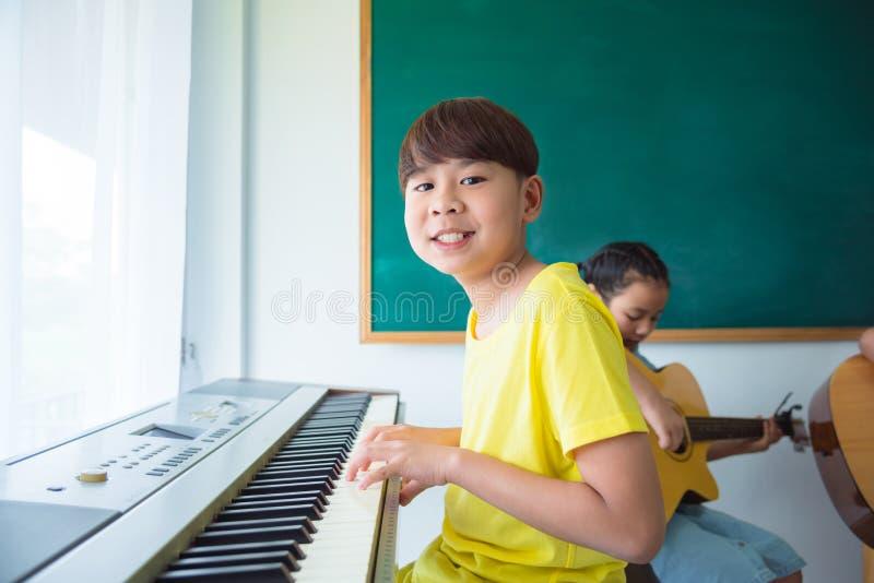 Menino que joga o teclado da música na escola fotos de stock royalty free