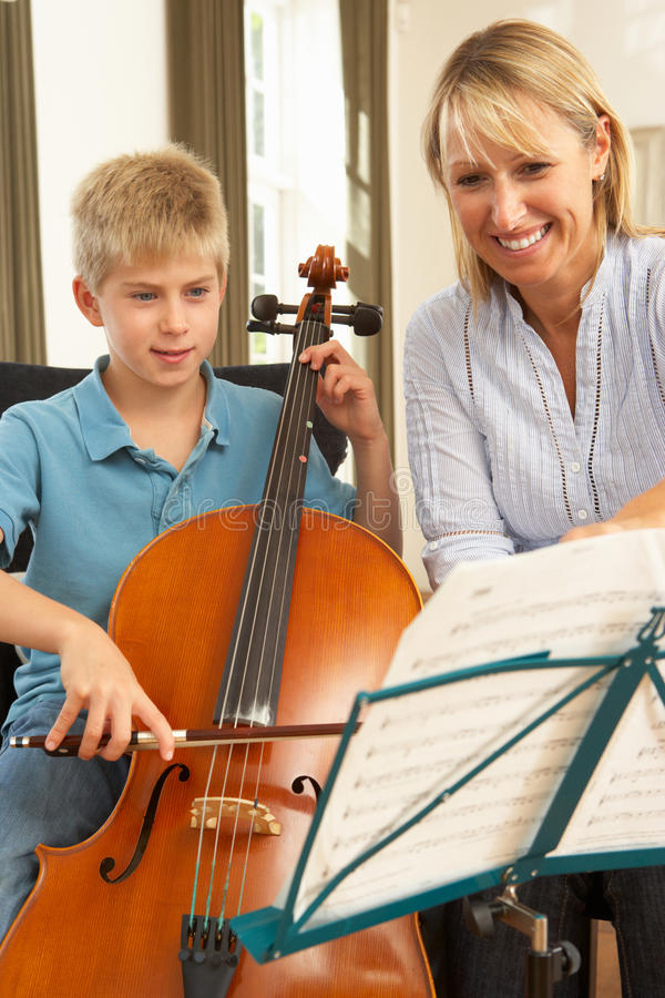 Menino que joga o violoncelo na lição de música imagens de stock