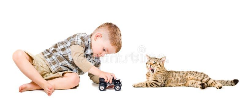 Menino que joga perto do gato imagens de stock