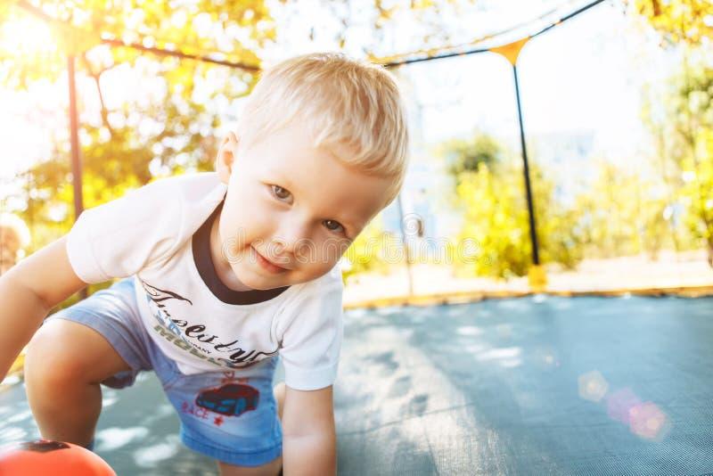 Menino que joga, saltando em um trampolim, olhando o sorriso da câmera imagens de stock royalty free