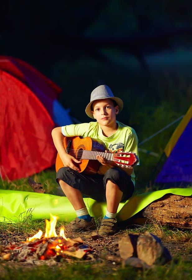 Menino que joga uma guitarra, acampamento de verão imagem de stock