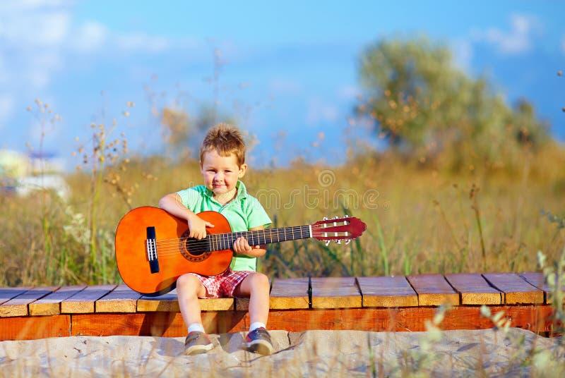 Menino que joga uma guitarra no campo do verão imagem de stock
