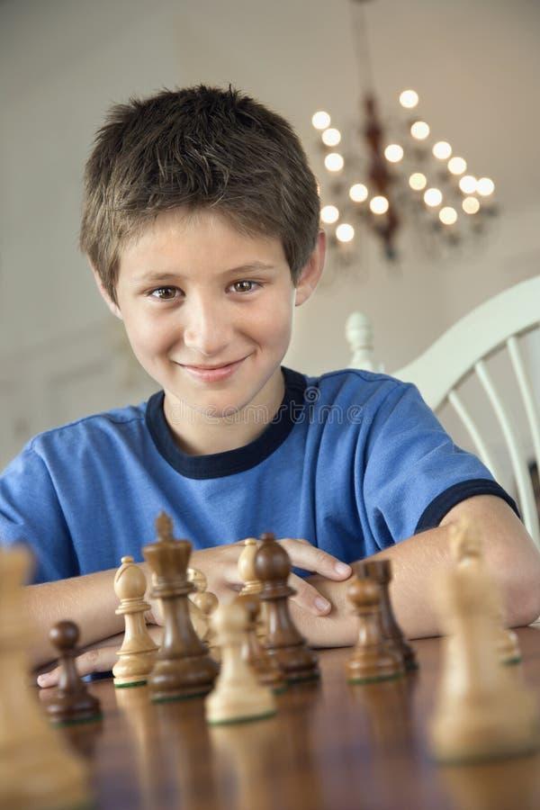 Menino que joga a xadrez. imagens de stock