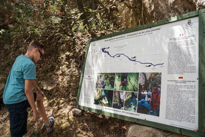 Menino que lê a tabela da informação sobre a mola - nascente de água, Oliena, Nuoro, Sardinia, Itália fotos de stock