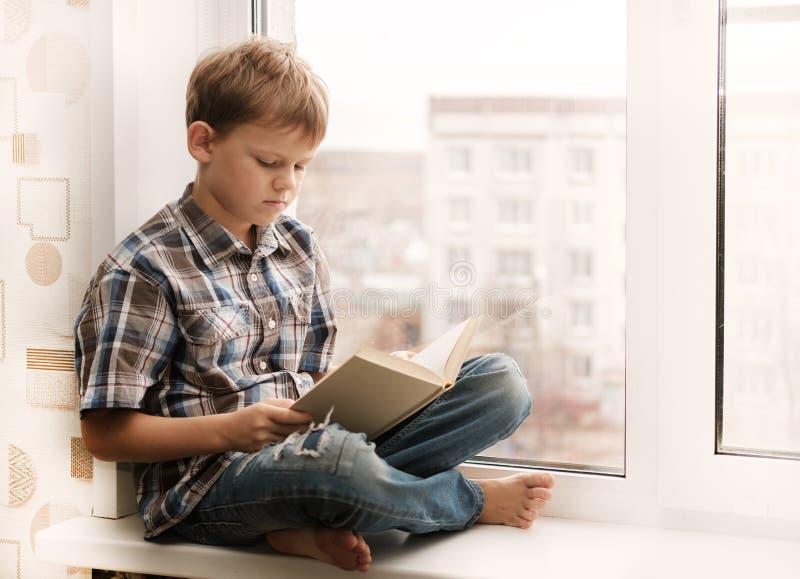Menino que lê um livro que senta-se na soleira fotografia de stock royalty free