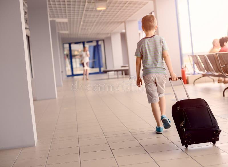 Menino que leva sua bagagem no aeroporto foto de stock