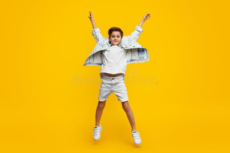 Menino que levanta as mãos e o salto imagens de stock royalty free
