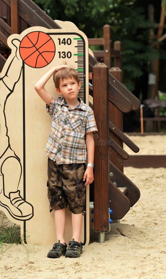 Menino que mede sua altura no campo de jogos fotografia de stock