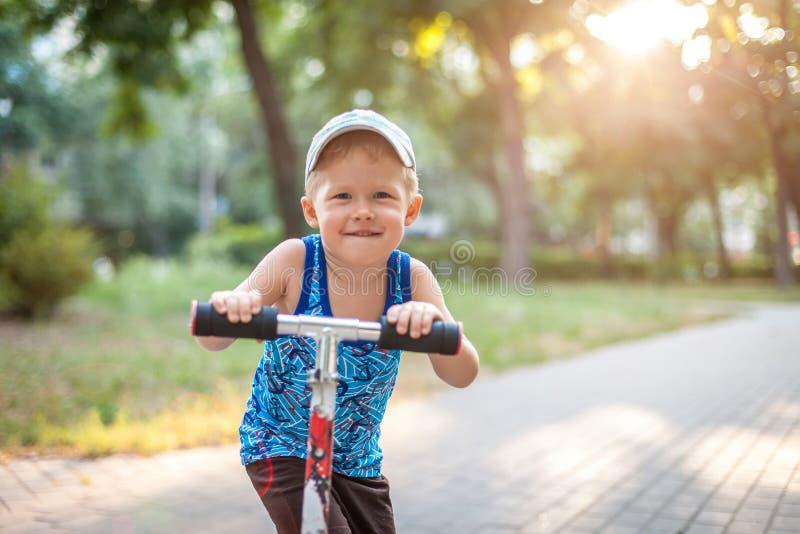 Menino que monta um 'trotinette' que olha a câmera, sorrindo, luminoso imagens de stock royalty free